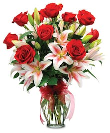 One dozen red roses with multiple stems of stargazer lilies arranged in a tall glass vase.