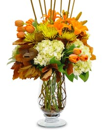 Tulips, Hydrangea, Lilies, Mums and Autumn accents in a sleek glass vase