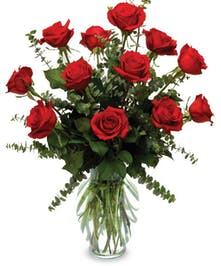 Long stemmed red roses with eucalyptus in a tall glass vase.