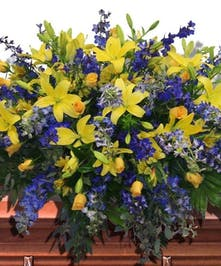 Golden-yellow lilies & roses with blue delphinium casket spray