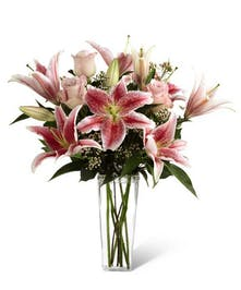 Pink roses, stargazer lilies and greens in a glass vase.