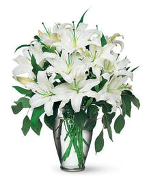 Stems of lovely white Oriental lilies are accented with seeded eucalyptus in a tall glass vase.