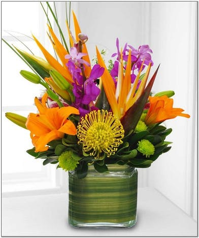 Brightly colored lilies, roses, sunflowers and more in a glass vase.