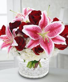 Red roses with stargazer lilies and hydrangea in a contemporary glass vase.