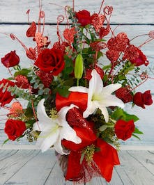 Dozen premium red roses accented with sparkly red hearts in vase