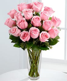 Two dozen pink roses with greenery and limonium in a tall vase