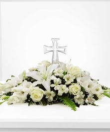 A beautiful white flower tribute with crystal cross