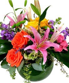Colorful roses with pink lilies and purple stock in vase