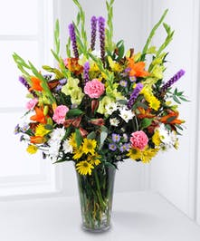 Colorful mix of a variety of fresh flowers in a tall vase