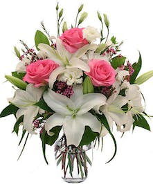 Pink roses and wax flower tucked in with white lily blooms in glass vase
