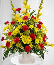 Yellow daisies & gladiolus, red carnations in sympathy urn
