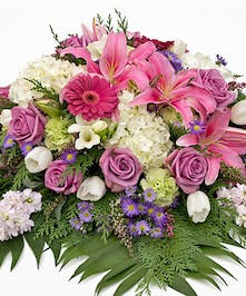 Pinks, purples and white lilies, hydrangea, tulips and stock casket spray