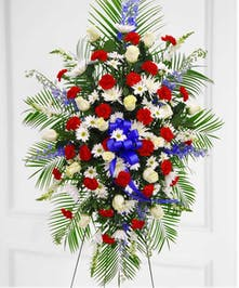 Red, white and blue flowers with palm fans and blue bow spray on easle