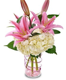Soft lilies, and hydrangea in cylindrical vase