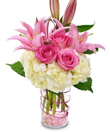 A pink and white display of Roses, Hydrangea and Oriental Lilies in a flirty vase.