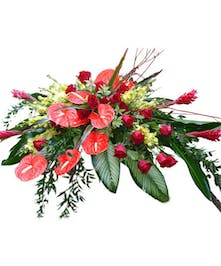 Red roses, red tropical blooms and greenery casket cover