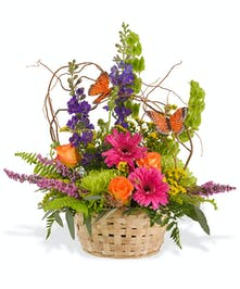 Bold colors of Gerbera Daisies, roses and garden flowers in basket ith butterflies