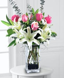 White lilies and pink roses with eucalyptus accent in a stylized glass vase.