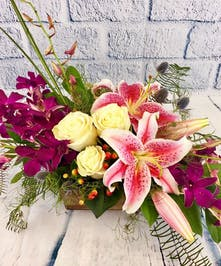 Stargazer lilies, white roses and purple orchids in centerpiece style