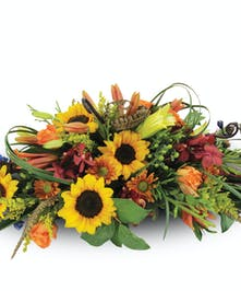 A centerpiece of sunflowers, lilies, orchids and daisies with feather accents