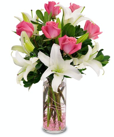 Pink roses sit nestled with white lilies in a cylindrical vase with pink accents.
