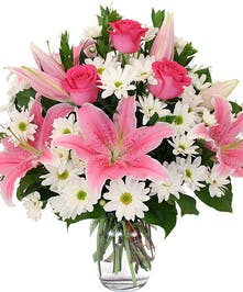 Stargazer lilies, pink roses and daisies in glass vase
