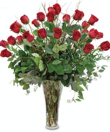 36 red roses with greens in a tall vase.