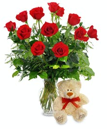 One dozen red roses in a tall vase with a cute plush bear.