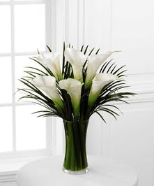 Tall white Calla Lilies and Palm leaves in a glass vase