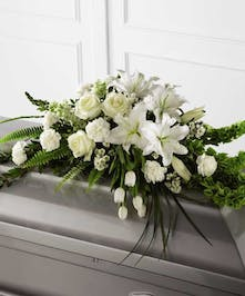 White roses, lilies, tulips, carnations with lacy greenery casket spray
