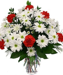White daisies, red carnations and greenery in glass vase