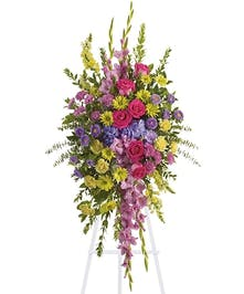 Full flower spray on easle with multi-colored garden-style flowers