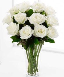 Arrangement of pure white roses and greenery in vase
