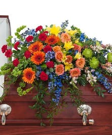 Roses, Fuji Mums, Gerbera Daisies, Delphinium in rainbow colors casket spray