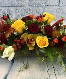 Autumnal colors of roses, orchids, tulips, dianthus, grains and grasses in centerpiece style