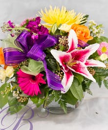Fresh mix of roses, stock, lilies, and assorted blooms in a compact bubble bowl vase.