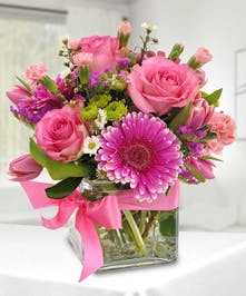 Pink Gerbera Daisies, roses and mini carnations in glass vase