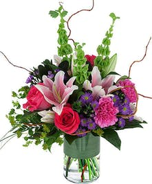 Fragrant flowers in pinks, purple, & lime green, compact design in vase