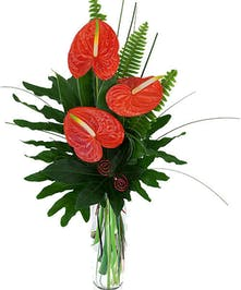 Tropical red Antherium with palm fans in vase