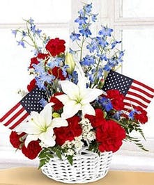 Patriotic colors of carnations, lilies and delphinium in basket with flags