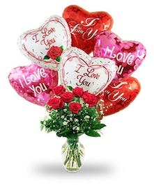 Red roses arranged in vase with love-themed balloons