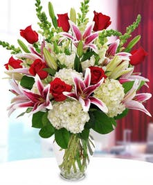 Stargazer Lilies, red roses, white hydrangea in large glass vase