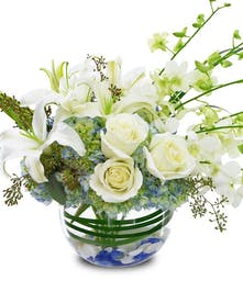 All white roses, hydrangea, orchids and lilies in a bubble bowl vase