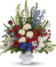Patriotic fan-style flowers featuring roses, delphinium and mums in urn