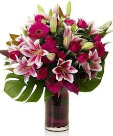 Large display of Stargazer Lilies, Gerbera Daisies, red roses,  in vase